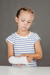 Young girl with broken arm is standing near the table.