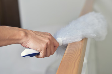 young man dusting the house with a microfiber duster