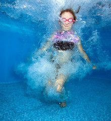 Young girl jumps and having fun in water.