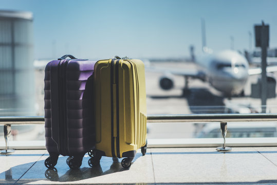 Two suitcases in the airport departure lounge, airplane in the blurred background, summer vacation concept, traveler suitcases in airport terminal waiting area