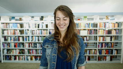 A young woman in a public library. It's her leisure time and she is looking for some good books to read.