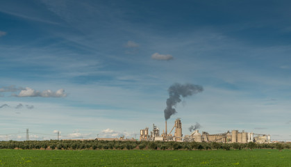 Green Field And Factory With Dark Smoke Coming Out Of Chimney