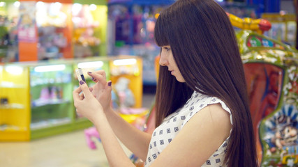Young woman playing Pokemon GO indoor at shopping center, using