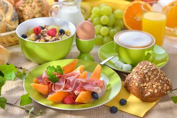Reichlich gedeckter Frühstückstisch mit Schinken und Melone - Laid breakfast table with melon and ham against a white background