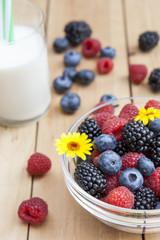Glass bowl of fresh blackberries, raspberries, blueberries and marigold on light wooden table