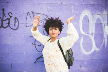 Half length of young handsome afro curly brown hair woman dancing in the city, listening music with earphones - freedom, music, carefree concept
