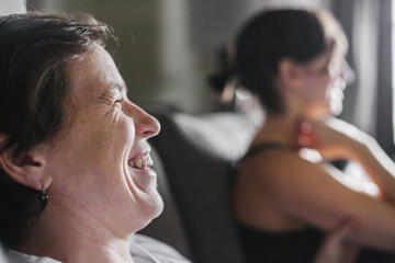 Two women in profile sitting at home, laughing.