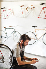 A man working in a bicycle repair shop sitting using his smart phone.