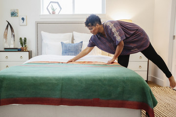 A woman smoothing a green fabric quilt  with red trim over a double bed in a light airy apartment.