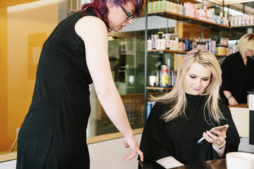 A hair stylist and a client, a young woman with long blonde hair, at a hair salon.