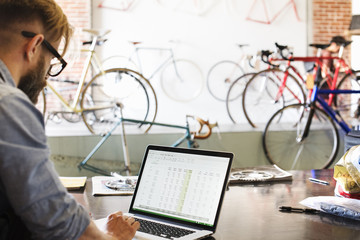 A man in a bicycle repair shop using a laptop computer.  Running a business.