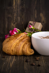 Fresh croissant and cappuccino over wooden table