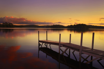 old pier in a lake at the sunset in maine - united states of america