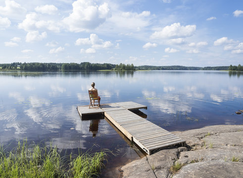 Young woman enjoying hot summer day in Finland next to lake