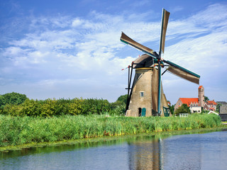 Foto op Canvas Molens Ancient wind mill reflected in blue canal on a summer day, Kinderdijk, The Netherlands.