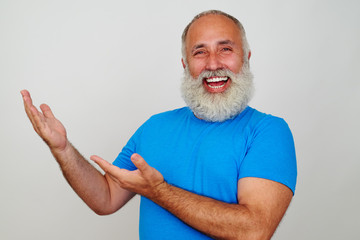 Cheerful bearded aged man pointing with his hands to one side