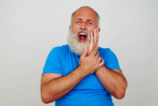 Bearded man touching his cheek as if having severe toothache