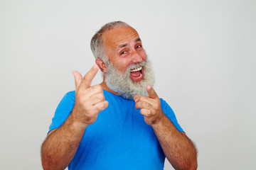 Good-looking elderly man energetically pointing at the camera