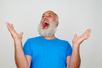 Portrait of bearded aged man who is happy and delighted
