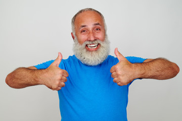 Smiling aged man giving two thumbs up against white background