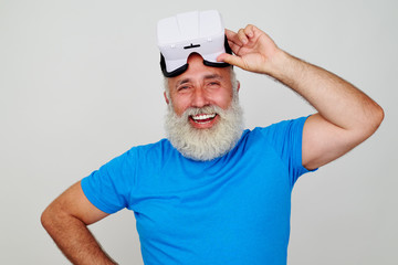 Smiling aged man satisfied by work of virtual reality headset