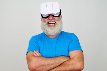 Smiling aged man with crossed arms wearing virtual reality heads