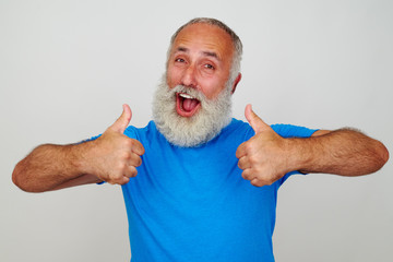 Smiling man with white beard giving two thumbs up