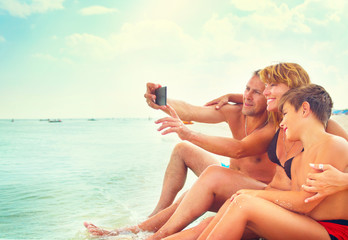 Happy young family sitting on the beach and taking selfie photo with smartphone