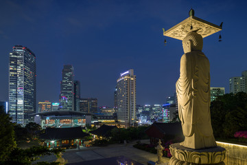 Mireuk Daebul statue (The Great Statue of Maitreya Buddha) at the Bongeunsa Temple and view of Gangnam in Seoul, South Korea at night.