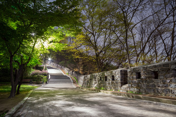 Walkway and fortress wall (or City Wall) at the Namsan Hill (or Namsan Park or Namsan Mountain) in Seoul, South Korea, at night.