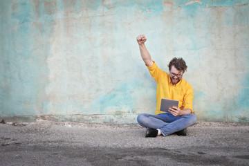Jubilant man holding a tablet