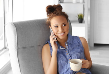 Beautiful African American girl with coffee and cellphone on armchair