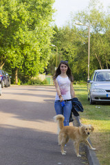 Girl walking a dog in summer day