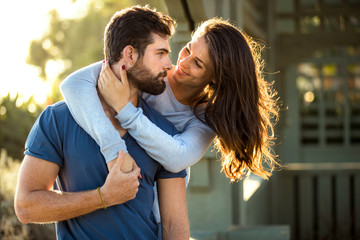 Handsome bearded man and brunette woman strong athletic lovers embrace at the park