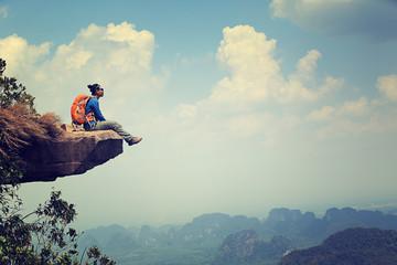 successful woman backpacker sit on mountain peak cliff