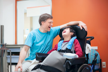 Disabled little boy in wheelchair talking with father in hospita