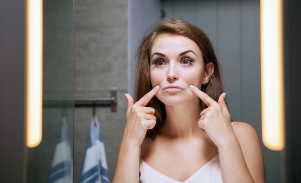Woman checking wrinkles on face in front of bathroom mirror