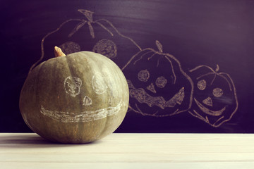 concept Happy Halloween/ Green pumpkin with a smile on blackboard painted with chalk cheerful pumpkins