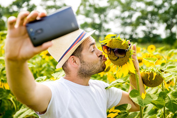 Man makes selfie in the field of sunflowers