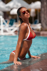 Sexy woman in swimming pool. Beautiful girl in the red bikini on the sun-tanned slim and shapely body