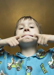Boy make grimace on his face. Boy ape and make strange face. Boy