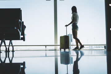 Young hipsetr girl standing near large window at the airport with suitcase while traveling in Europe, attractive female traveler waiting flight at departure lounge