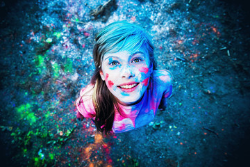 The girl in the colors of Holi smiling