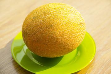 Fresh yellow ripe melon on a green plate