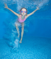 Small girl jumps and having fun in water.