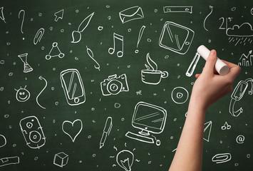 Hand writing icons on blackboard