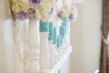 Floral arrangement with white and blue flowers and candles on candle holders. Wedding decor idea.