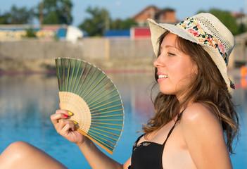 Girl in bikini holding a hand fan by the pool