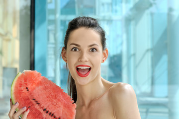 Girl is posing with a slice of red watermelon