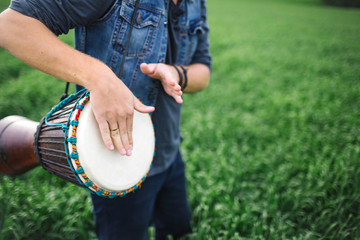 Male playing ethnic drum outdoors